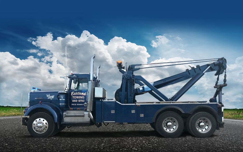 Eastland Towing blue 45 ton heavy-duty wrecker with a 45 ton boom that allows it to lift 90,000 lbs. Big Holmes winches for pulling heavy equipment and vehicles out of the mud.