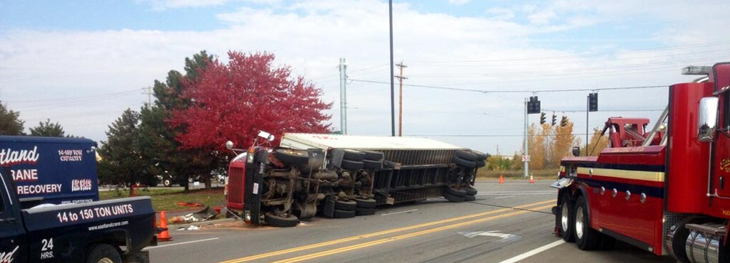 Eastland Towing heavy-duty wrecker and heavy recovery vehicles on the scene assisting an overturned tractor trailer.