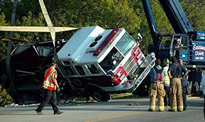 Crane assists in up-righting a truck using large straps.
