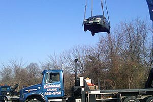 Lifting a vehicle out of a water retention pond in the woods using a crane.